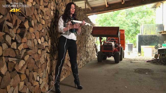Nipple rings and leather thigh boots Miss Hybrid in the wood shed.
